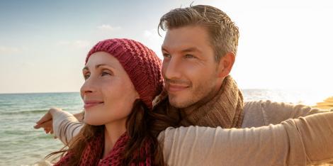 Paar steht am Strand und genießt die Luft