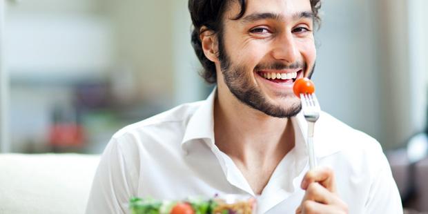 Ein Mann isst Salat