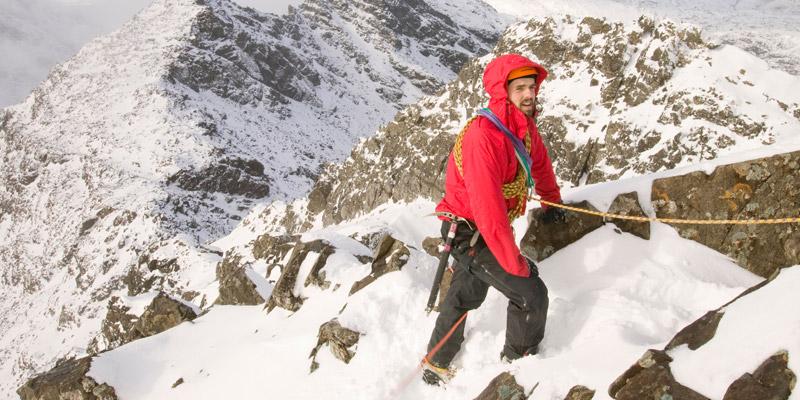 Ein Bergsteiger besteigt einen Berg im Schnee
