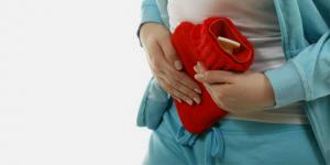 Eine Frau hält sich eine Wärmflasche an den Bauch