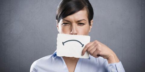 Eine Frau hält sich einen Zettel mit einem traurigen Mund vors Gesicht
