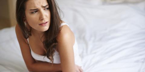 Eine Frau sitzt mit Bauchkrämpfen auf dem Bett