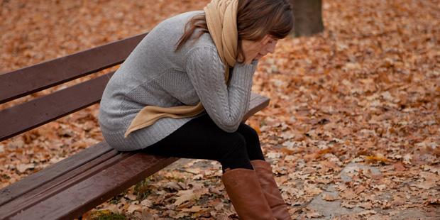 Eine Frau sitzt traurig auf einer Bank