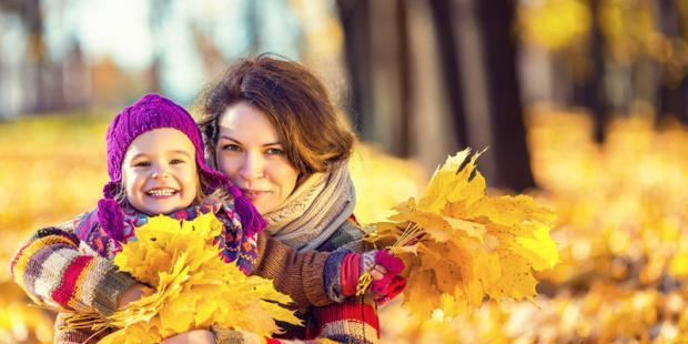 Mama mit Kind im Herbstlaub