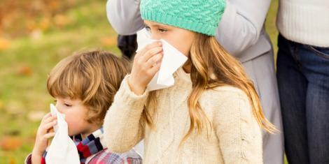 Junge und Mädchen mit Schnupfen putzen sich die Nase