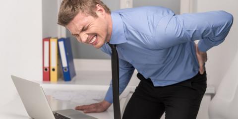 Ein Mann steht vom Schreibtisch auf und hält sich den Rücken