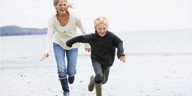 Eine Mutter spielt mit ihrem Sohn im Watt fangen