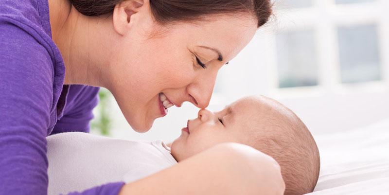 Mutter liebkost ihr Neugeborenes