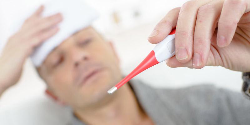 Mann mit Fieberthermometer