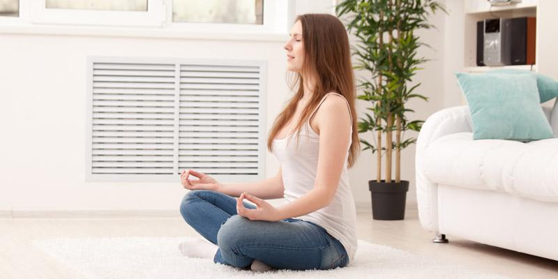 Frau macht Yoga um Rückenschmerzen vorzubeugen